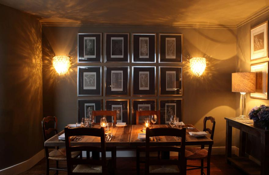 Dining table with arrangement of wall pictures and lighting